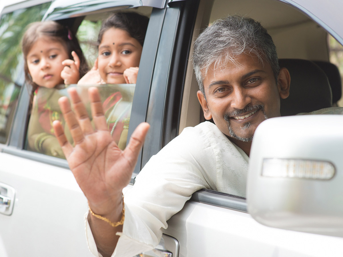 Indian family waving goodbye in a car