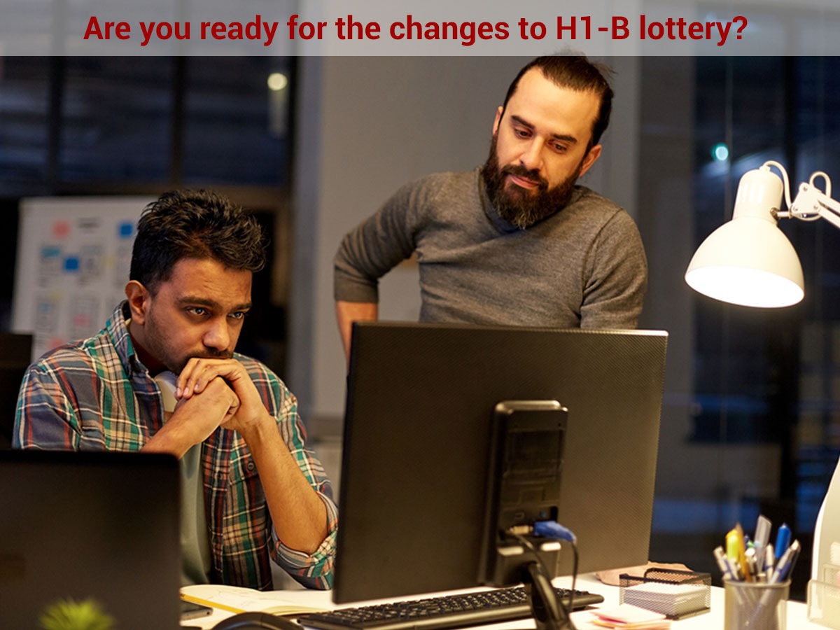 Two men analyzing changed to H1B lottery on a computer screen